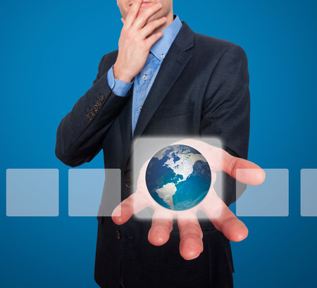 Earth in front of businessman.Touch screen consept . blue background - Stock Image photo