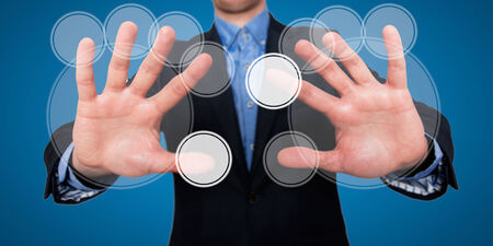 emanate: A businessman in front of a visual touch screen is illustrating the concept of the technology. He has his two arms extended and his fingers are touching the space in front of him. Several circular icons emanate from his point of touch. Stock Photo