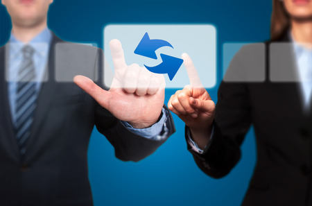 refresh button: Businessman and Businesswoman touching Refresh button and Ticking Check Box concept on a visual screen. The woman is dressed in a vest. Blue background Stock Photo