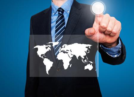Businessman in dark suit pushing button worldmap global communication. Blue background Imagens