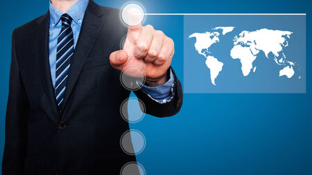 worldmap: Businessman in dark suit pushing button worldmap global communication. Blue background Stock Photo