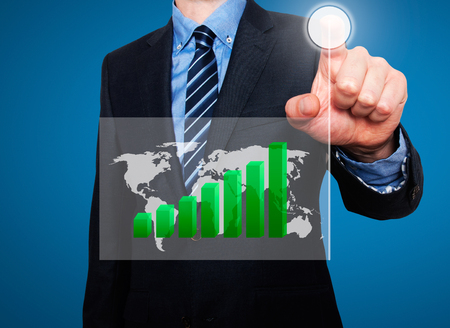 worldmap: Businessman in dark suit pushing button worldmap global Growth. Green Graph going up. Blue background Stock Photo