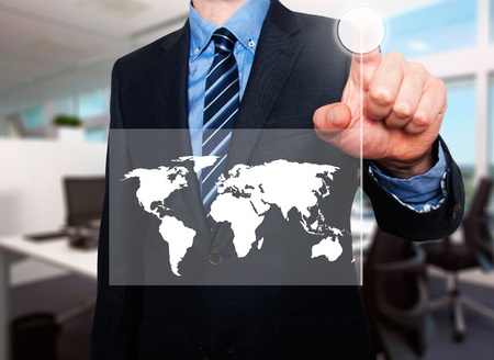 worldmap: Businessman in dark suit pushing button worldmap global communication. office background Stock Photo