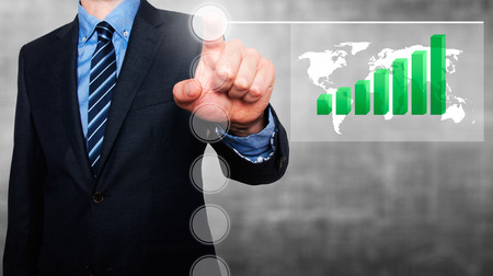 worldmap: Businessman in dark suit pushing button worldmap global Growth. Green Graph going up. grey background