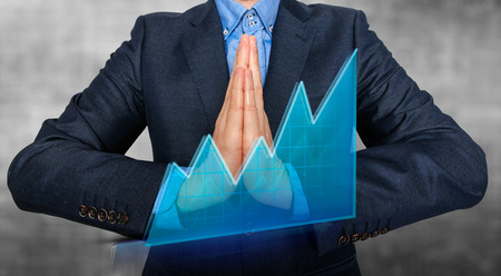 Young Man Businessman praying and Wishing Hard. Graph in front. Grey background - Stock Image photo