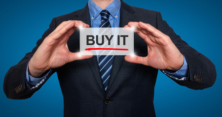 preorder: Businessman in black suit holding buy it sign. Blue background