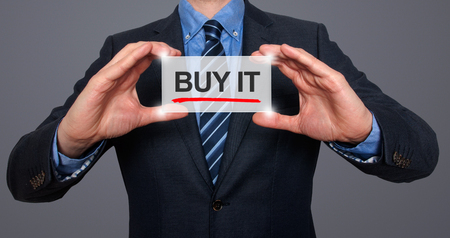 Businessman in black suit holding buy it sign. Grey background Stock Photo