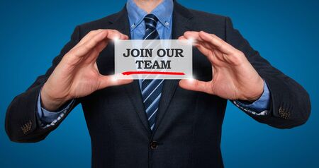 Businessman holding white card with Join our team sign, Blue background