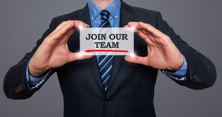 Businessman holding white card with Join our team sign, Grey background