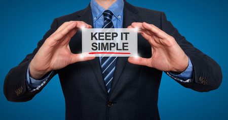 Keep It Simple in a navigation bar on a virtual screen with a businessman holding it. Blue background