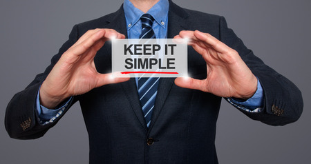 Keep It Simple in a navigation bar on a virtual screen with a businessman holding it. Grey background Stock Photo