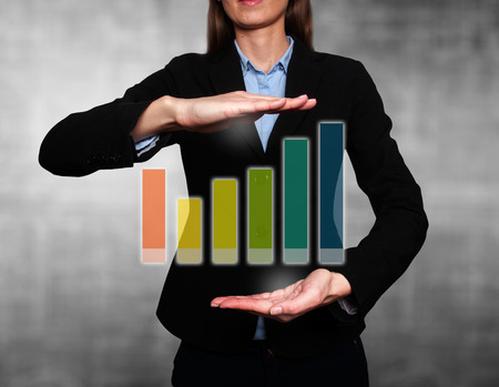 Businesswoman holding futuristic Growth graph. Grey background. Stock Image