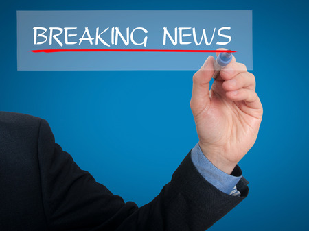 media event: Businessman writing breaking news in the air. Grey background Stock Photo