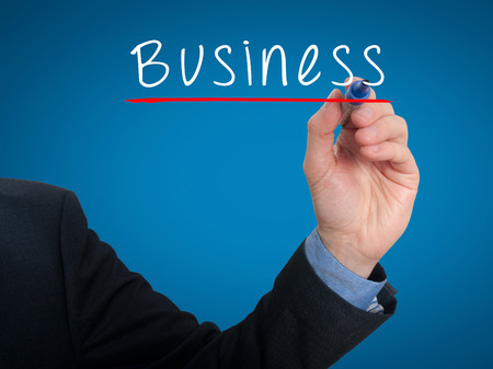 Businessman writing Business in the air - Stock Image. Blue Background photo