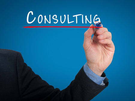 Businessman hand writing Consulting. Consult sign for business. blue background.