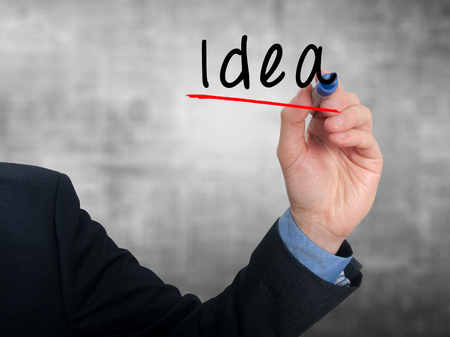 Business man writing Idea in the air. Blue background photo