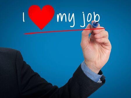 Businessman writing I love my job with heart shape. Blue background