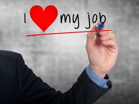 Businessman writing I love my job with heart shape. Grey background Stock fotó - 36881716