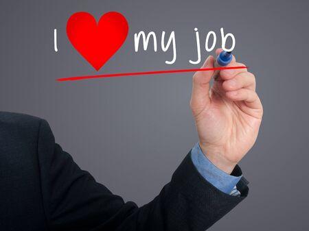 Businessman writing I love my job with heart shape. Grey background