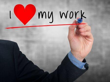 heart work: Businessman writing I love my work with heart shape. Grey background