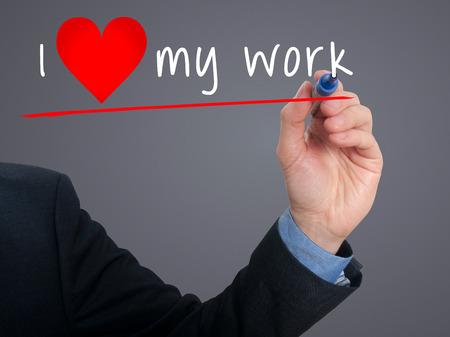 Businessman writing I love my work with heart shape. Grey background