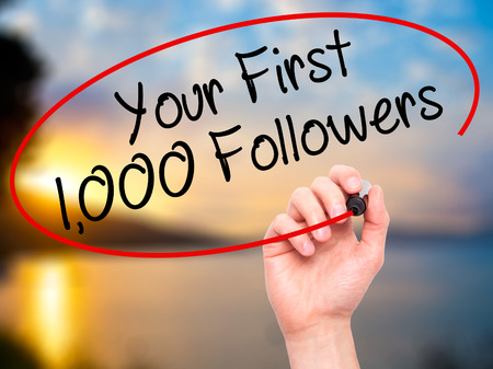 Man Hand writing Your First 1,000 Followers  with black marker on visual screen. Isolated on nature. Business, technology, internet concept. Stock Photo Stock Photo