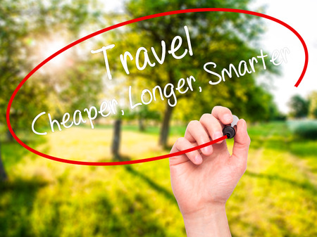 longer: Man Hand writing Travel Cheaper Longer Smarter  with black marker on visual screen. Isolated on nature. Business, technology, internet concept. Stock Photo