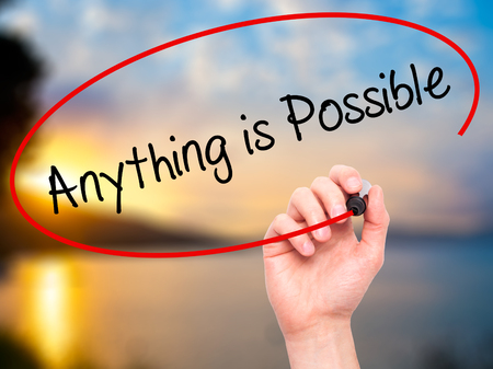 anything: Man Hand writing Anything is Possible with black marker on visual screen. Isolated on nature. Business, technology, internet concept. Stock Photo