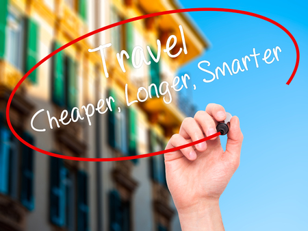 cheaper: Man Hand writing Travel Cheaper Longer Smarter  with black marker on visual screen. Isolated on city. Business, technology, internet concept. Stock Photo