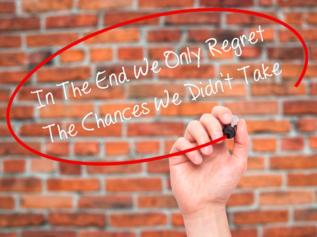 chances: Man Hand writing In The End We Only Regret The Chances We Didnt Take with black marker on visual screen. Isolated on bricks. Business, technology, internet concept. Stock Photo