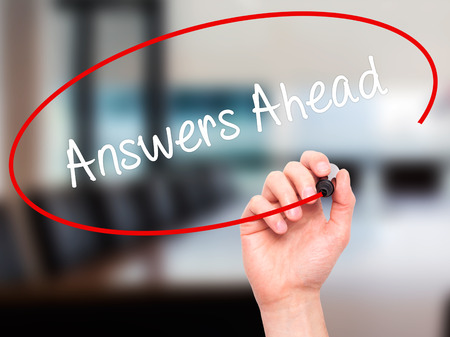 qa: Man Hand writing Answers Ahead with black marker on visual screen. Isolated on office. Business, technology, internet concept. Stock Photo