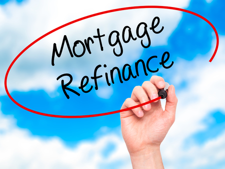 Man Hand writing Mortgage Refinance with black marker on visual screen. Isolated on sky. Business, technology, internet concept. Stock Photo