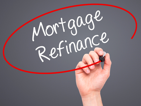 refinance: Man Hand writing Mortgage Refinance with black marker on visual screen. Isolated on grey. Business, technology, internet concept. Stock Photo Stock Photo