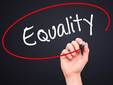 impartial: Man Hand writing Equality  with black marker on visual screen. Isolated on black. Business, technology, internet concept. Stock Photo