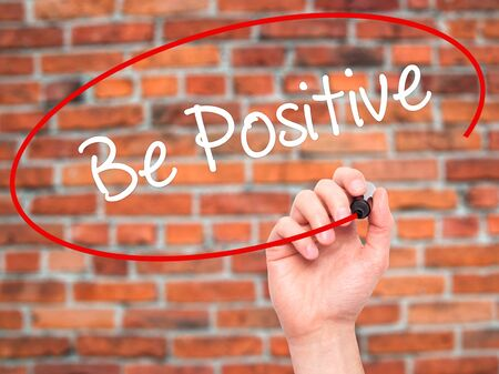 persist: Man Hand writing Be Positive  with black marker on visual screen. Isolated on bricks. Business, technology, internet concept. Stock Photo
