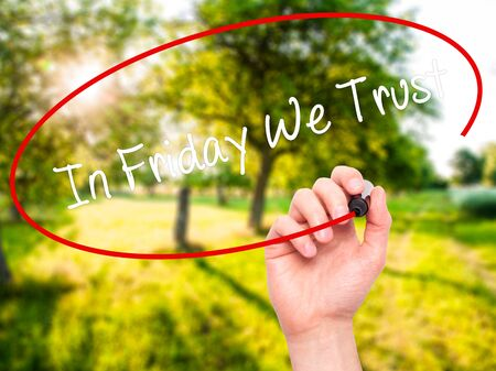 positiveness: Man Hand writing In Friday We Trust  with black marker on visual screen. Isolated on nature. Business, technology, internet concept. Stock Photo