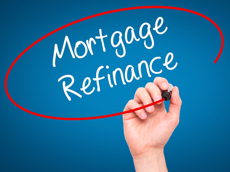 refinance: Man Hand writing Mortgage Refinance with black marker on visual screen. Isolated on blue. Business, technology, internet concept. Stock Photo Stock Photo