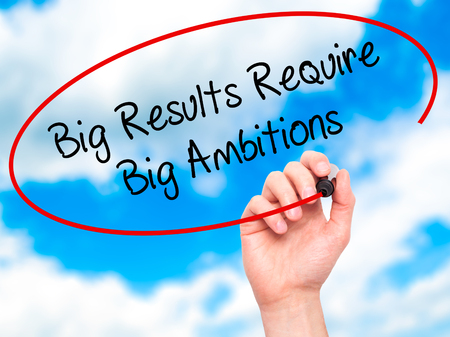 require: Man Hand writing Big Results Require Big Ambitions with black marker on visual screen. Isolated on sky. Business, technology, internet concept. Stock Photo