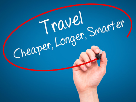 cheaper: Man Hand writing Travel Cheaper Longer Smarter  with black marker on visual screen. Isolated on blue. Business, technology, internet concept. Stock Photo