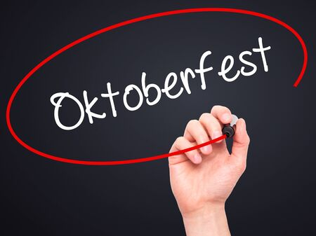prost: Man Hand writing Oktoberfest with black marker on visual screen. Isolated on black. Business, technology, internet concept. Stock Photo