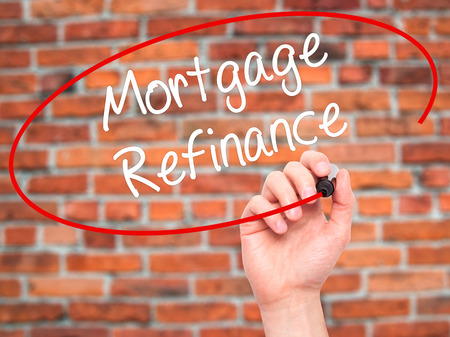 refinance: Man Hand writing Mortgage Refinance with black marker on visual screen. Isolated on bricks. Business, technology, internet concept. Stock Photo Stock Photo