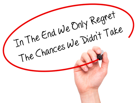 chances: Man Hand writing In The End We Only Regret The Chances We Didnt Take with black marker on visual screen. Isolated on white. Business, technology, internet concept. Stock Photo