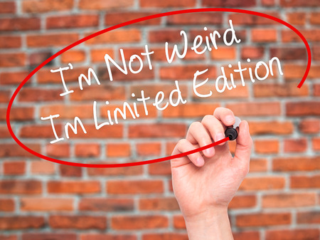 wacky: Man Hand writing Im Not Weird Im Limited Edition with black marker on visual screen. Isolated on bricks. Business, technology, internet concept. Stock Photo