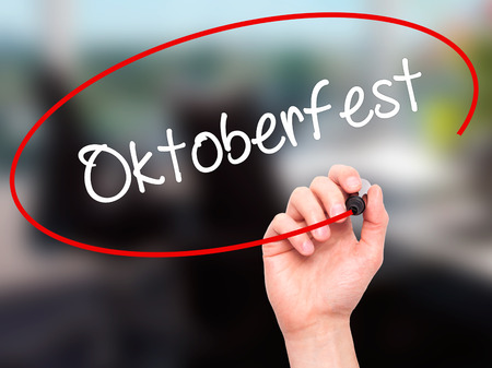 bier festival: Man Hand writing Oktoberfest with black marker on visual screen. Isolated on office. Business, technology, internet concept. Stock Photo