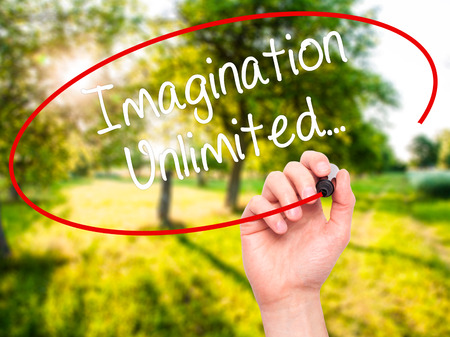 unlimited: Man Hand writing Imagination Unlimited... with black marker on visual screen. Isolated on nature. Business, technology, internet concept. Stock Photo