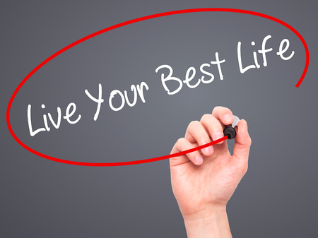 motivator: Man Hand writing Live Your Best Life with black marker on visual screen. Isolated on grey. Business, technology, internet concept. Stock Photo Stock Photo