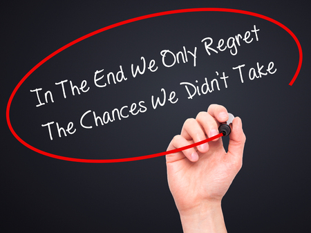 chances: Man Hand writing In The End We Only Regret The Chances We Didnt Take with black marker on visual screen. Isolated on black. Business, technology, internet concept. Stock Photo Stock Photo