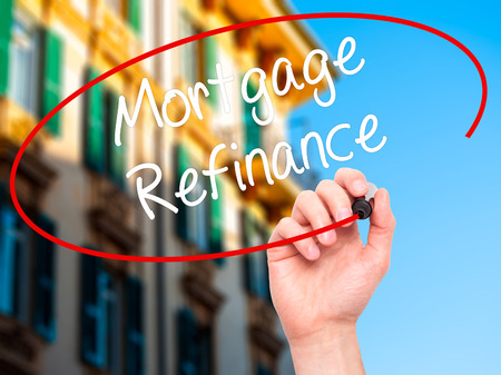 refinance: Man Hand writing Mortgage Refinance with black marker on visual screen. Isolated on city. Business, technology, internet concept. Stock Photo