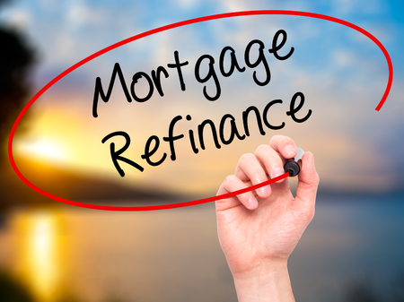 Man Hand writing Mortgage Refinance with black marker on visual screen. Isolated on nature. Business, technology, internet concept. Stock Photo