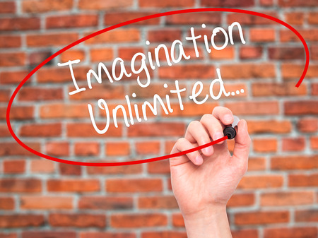unlimited: Man Hand writing Imagination Unlimited... with black marker on visual screen. Isolated on bricks. Business, technology, internet concept. Stock Photo